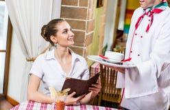 Uppassaren kommer med en maträtt för en trevlig kvinna Royaltyfri Foto