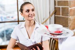 Uppassaren kommer med en maträtt för en trevlig kvinna Arkivfoto