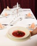 Uppassaren kommer med Ukraina och ryssen traditionell soppa på tabellen, borscht Fotografering för Bildbyråer