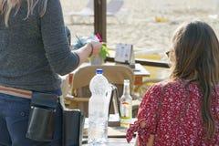 Uppassaren räknar kunden i ett kafé på stranden royaltyfri fotografi