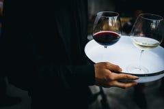 Uppassaren rymmer ett magasin med exponeringsglas av rött vin royaltyfria foton