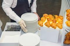 Uppassaren servering sköta om buffétabellen med mat och mellanmål för gäster av händelsen Äta middag begrepp för matberömparti arkivbilder