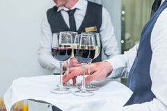 Uppassaren servering sköta om magasinet med alkoholisten, och icke-alkoholisten dricker på affärshändelsen i korridoren Service p arkivbilder