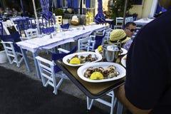 Uppassaren tjänar som den grillade tioarmade bläckfisken på plattan i en restaurang Arkivbild