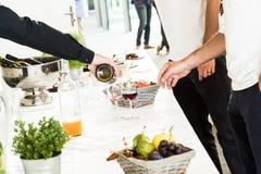 UppassarePouring Red Wine exponeringsglas till två män på den vita buffétabellen arkivbild
