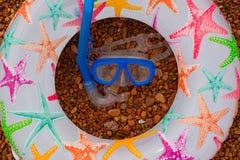Uppblåsbar behandla som ett barn snorkeln för maskeringen för cirkelsandaler den undervattens-, lögn på stranden royaltyfria bilder