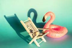 Uppblåsbar flamingo och deckchair på en blå bakgrund, pölflöteparti, royaltyfri foto