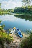 Uppblåsbara fartyg på den pebbly banken av floden Kajaker i klart vatten Royaltyfri Foto