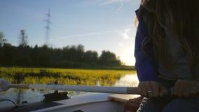 Uppblåsbart fartyg för ung lycklig flickarodd för blandat lopp med träåror på sjön med solnedgång på bakgrund Slowmotion HD arkivfilmer