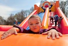 uppblåsbar glidbana för pojke Arkivbilder