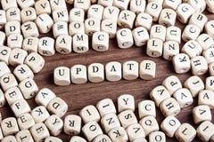 Uppdateringen bokstav tärnar ord arkivfoto
