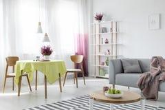 Uppehälle och matsal i lägenhet med den gråa soffan och trämöblemang, verkligt foto royaltyfri bild