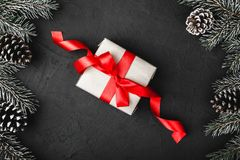 Upper, above, top view of pine, evergreen, and Christmas center present with red ribbon on stone background. royalty free stock images