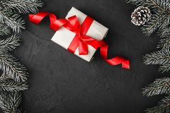Upper, above, top view of pine, evergreen, and Christmas present with red ribbon on stone background. stock photo