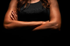 Upper body of a muscular woman. In a studio stock photo