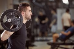 Upper body shot, squat exercise close up,. Young man holding barbell with weights on back shoulders. Unrecognizable people behind in gym out of focus royalty free stock photography
