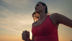 Upper body of a slim young woman during running session in a close up stock video footage