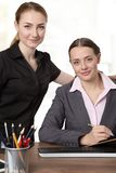 Friendly work collegues. Upper body studio shot of two pretty, business models at a desk looking at camera Royalty Free Stock Photos