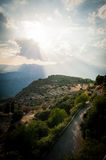 Upper Central Greece, August 2015, Delphic moutains panorama in a beautiful sun through clouds. Panorama done from one of city restaurant Royalty Free Stock Photos