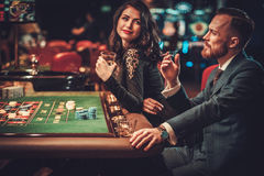 Upper class couple gambling in a casino.  stock image