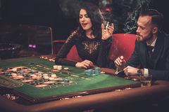 Upper class couple gambling in a casino. Upper class friends gambling in a casino Royalty Free Stock Photos