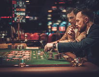 Upper class friends gambling in a casino Stock Image