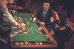 Upper class friends gambling in a casino.  Royalty Free Stock Images