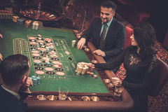 Upper class friends gambling in a casino Royalty Free Stock Photos