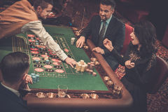 Upper class friends gambling in a casino.  Stock Photos