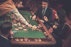 Upper class friends gambling in a casino Stock Photos