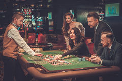 Upper class friends gambling in a casino.  Stock Image