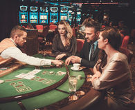 Upper class friends gambling in a casino.  Royalty Free Stock Photos