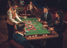 Upper class friends gambling in a casino royalty free stock images