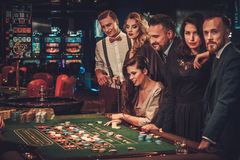 Upper class friends gambling in a casino.  royalty free stock image