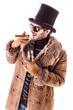 Upper class hustler. A young man wearing a sheepskin coat isolated over a white background holding a cigar and a glass with champagne Stock Images