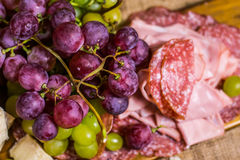 Upper close view of salami, mortadella, yellow and red muscat grape on a wooden board and canvas Stock Images