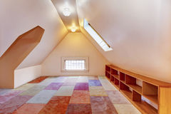 Upper empty room with vaulted ceiling and colourful carpet Royalty Free Stock Image