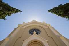 Upper facade of Church. Low Angle shot of the top of a church, with a view of the sky illuminated by a heavenly gleam, along with two cypresses Royalty Free Stock Photo