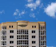 The upper floors of multistory building. Against the blue sky with clouds stock photo