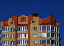 The upper floors of multistory building. Against the blue sky with clouds royalty free stock image