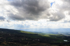 Upper Galilee mountains landscape. Heights, overcast weather, sunlight rays and shadows, green fields Royalty Free Stock Photography