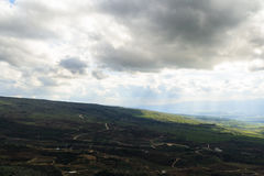 Upper Galilee mountains landscape. Heights, overcast weather, sunlight rays and shadows, green fields Royalty Free Stock Images