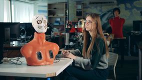 Upper half of a cyborg`s body and a young woman operating a laptop stock video