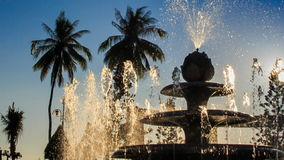 Upper jet of round cascade fountain sprays in tropical park stock video