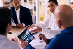 Upper management meeting between four board members with electronic tablet. Business meeting between four upper management board members in the new modern office Royalty Free Stock Photo