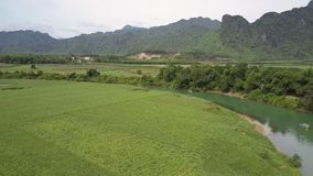 Upper motion along curve river with fields on steep banks. Perfect upper motion along curve river with fields on steep banks and small country houses among trees stock footage