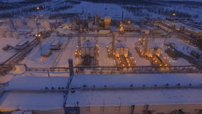 Upper Motion to Big Light Plant at Winter Night. Aerial view on brightly lit and covered with snow gas plant constructions with pipes workshops at winter night stock video