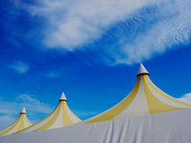 Upper part of a big colorful plastic tent. Blue sky and white clouds in background Stock Photography