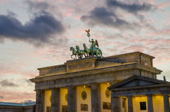 Upper part of Brandenburger Tor in Berlin with pink evening light and soft clouds, winter, Germany. Brandenburger Tor in Berlin with pink evening light and soft stock photo