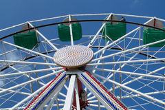 Upper part of ferris wheel with green and blue bowls. Against blue sky Royalty Free Stock Photo